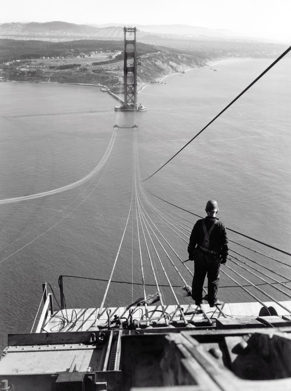1935 - A man standing on the first cables during the construction of the Golden Gate Bridge, with the Presidio and San Francisco in the background.