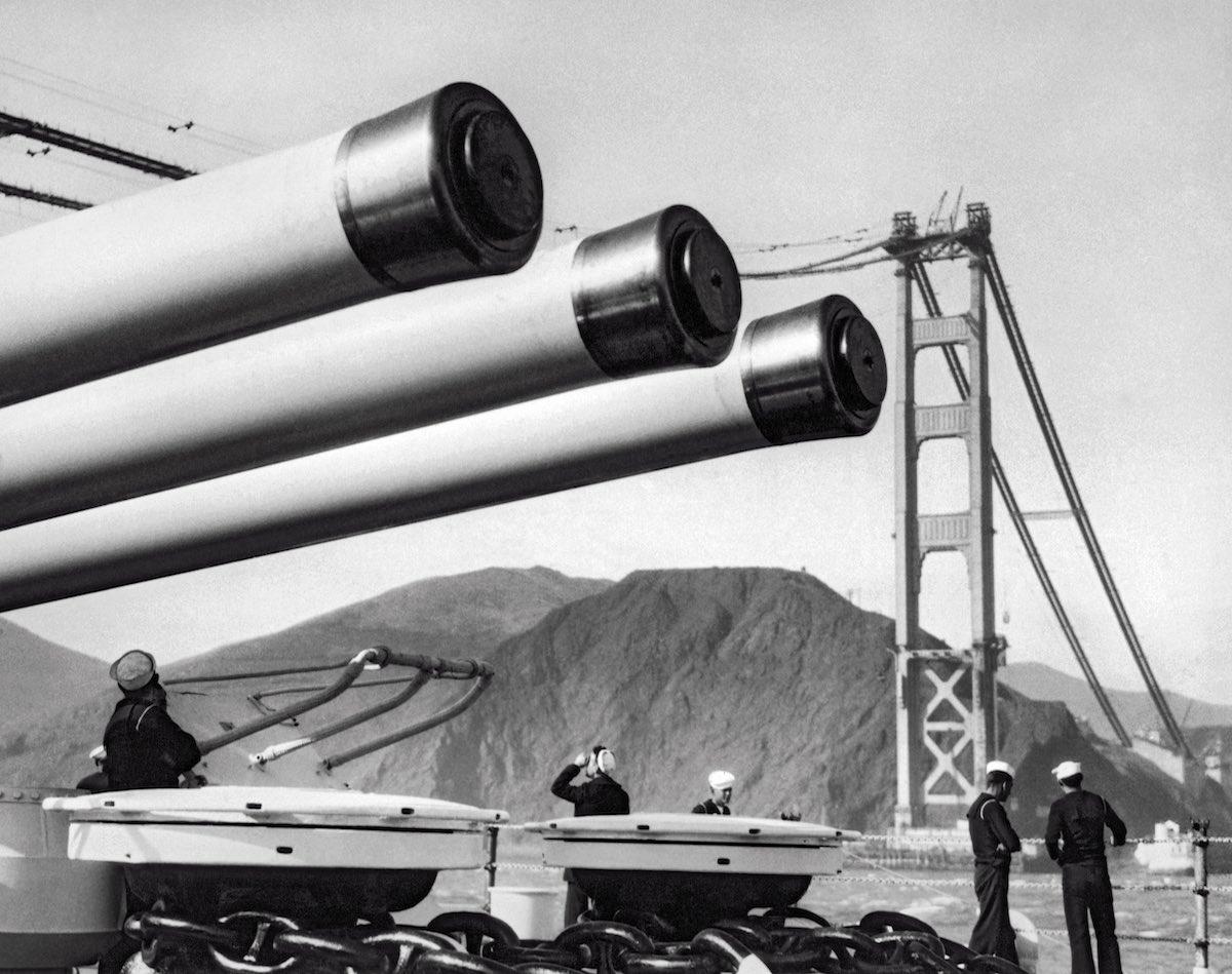 1936 - Um navio de guerra da Marinha dos EUA cruzeiros sob os cabos da ponte durante a construção.