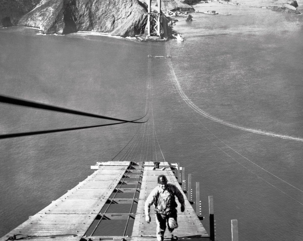 19 de setembro de 1935 - Um trabalhador subindo um das passarelas que estavam sendo construídas para sustentar os cabos